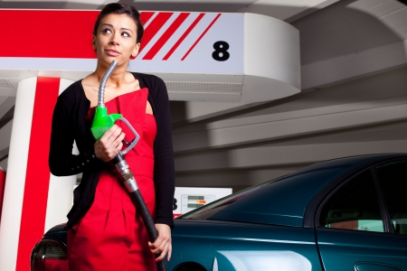 petrol stations: Young woman pumping fuel in her car on gas station Stock Photo