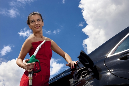 fuels: Young woman with fuel nozzle on gas station with black car and sky Stock Photo