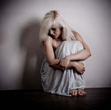 anguish: Scared woman sitting by the empty wall Stock Photo
