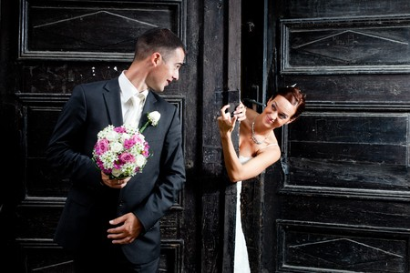 Bride behind the big old wooden gate calling the groom holding the flowers Stock Photo - 8092641