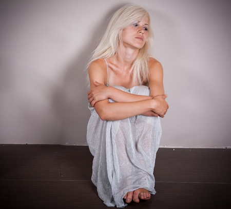 Sad woman sitting by the empty wall photo