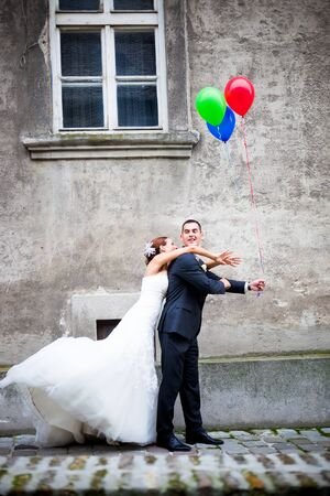 Wedding couple in love having fun. Groom is hiding the balloons from the bride Standard-Bild