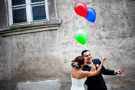 Couple in love having fun. Man hiding the balloons from the woman