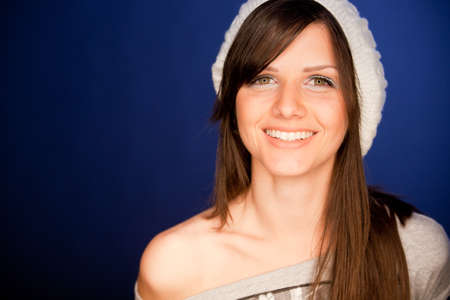 Beautiful young woman portrait, smiling against simple blue background