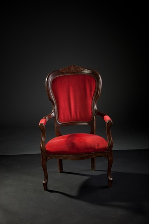 Old baroque armchair on black paper studio background with dusty footprints around