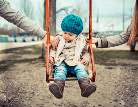 swinging: Sad child on a swing, inbetween her  divorced parents holding her separatedly