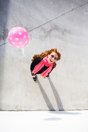Bright happy woman holding a balloon and posing
