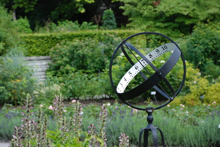 Sundial on the flowerbed in the park Stock Photo