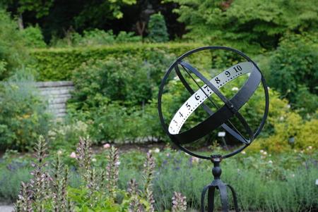 reloj de sol: Sundial on the flowerbed in the park Foto de archivo