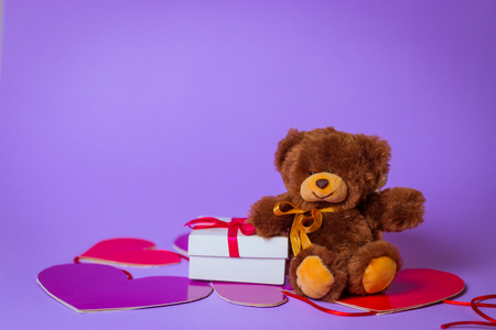 Toy Bear sits on paper hearts near a white gift box with a Red Ribbon on a purple background. Stockfoto