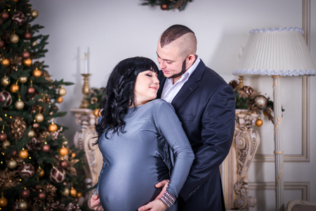 Happy family. Husband lovingly hugs his pregnant wife on the background of the Christmas tree and fireplace. Stockfoto