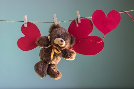 Toy Teddy bear are suspended from the rope clothespins on a background of white clouds Stock Photo