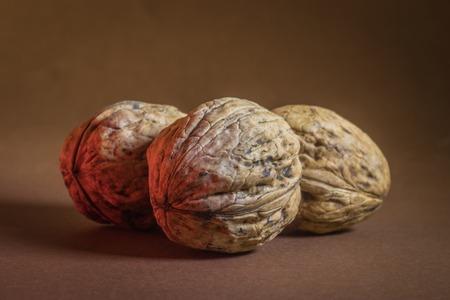 three Walnut walnuts on a dark brown background. Reklamní fotografie - 115557389