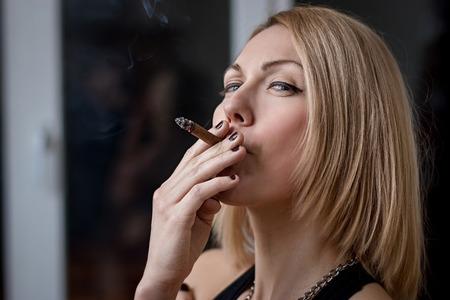 Beautiful girl smokes at night at the window. Stok Fotoğraf