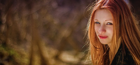 Portrait of a red-haired beautiful girl in forest.