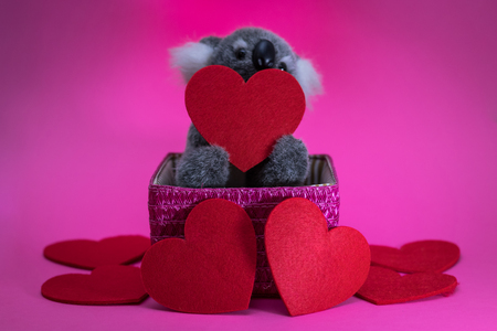 cute toy koala with red heart on pink basket. Banque d'images - 115557137
