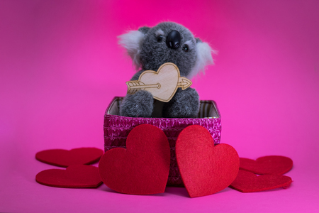 cute toy koala with wooden heart on pink basket. Banque d'images - 115557138