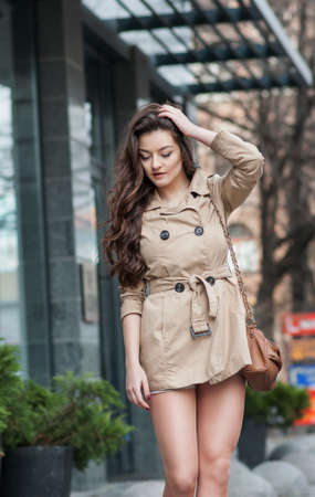 pretty young girl in casual style walking on the city street.