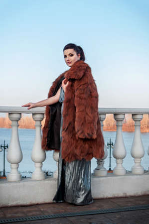 outdoor glamour: fashion outdoor photo of sexy glamour woman with dark hair wearing luxurious fur coat and leather gloves,posing Stock Photo