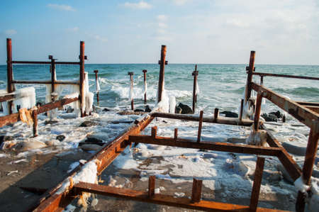 widening: Frozen winter sea with wooden pole. Horizontal.