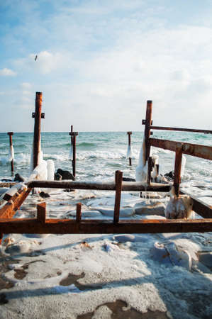 widening: Frozen winter sea with wooden pole. Vertical. Stock Photo