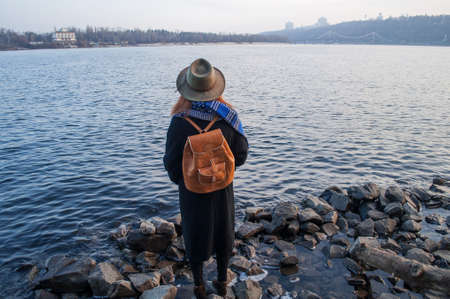 rucksack ': Young woman in hat and with rucksack standing on the riverbank, looking at sunset or sunrise on horizon, back view, copy space.