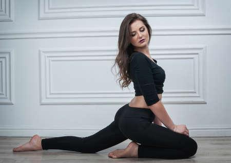 Beautiful girl sitting on floor against white background. Stock Photo
