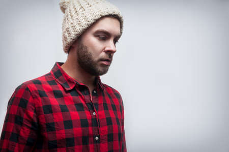 Brutal bearded man wearing knitted cap and plaid shirt. Stock Photo