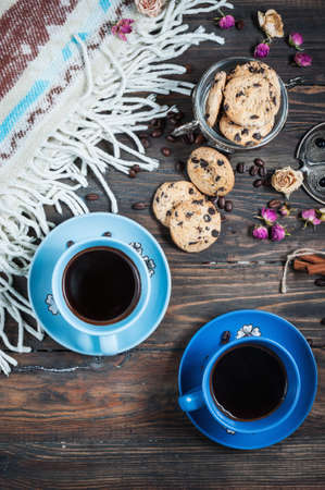 table decoration: The cup of coffee, coffee beans and cookies-hearts related together on  wooden table.