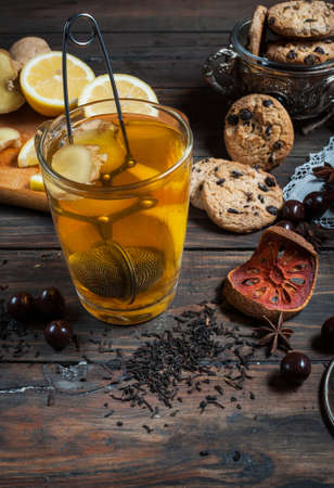 breakfast cup: Dried tea with lemon and cookies on wooden table.