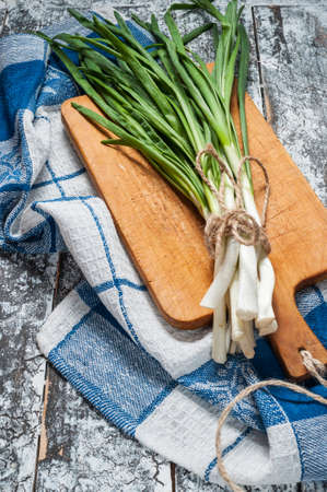 bunch of: bunch of spring onion on a wood table.