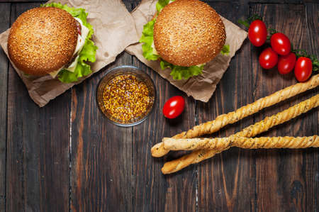 gressins: Fresh homemade burgers and breadsticks on wooden background. Banque d'images