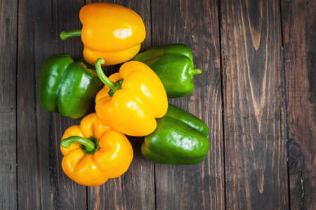 abreast: yellow and green paprika on wood background.