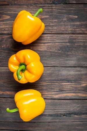 abreast: yellow paprika on wood background. close up. Stock Photo