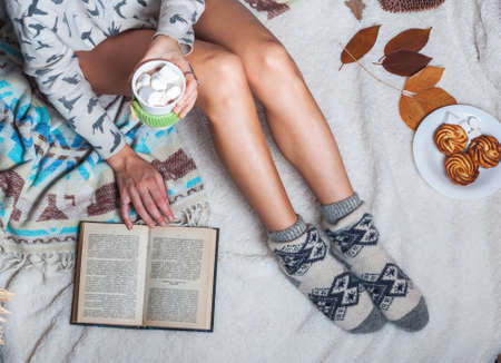 female legs: Long female feet in warm woolen socks around her feet is a book she is reading it. Part of the body. Beautiful female legs sitting on the bed with a cup. Morning with a book