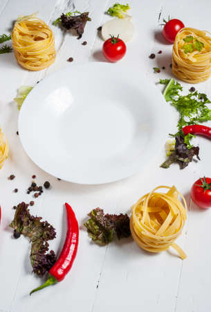 owning: Ingredients for cooking spagetti, cherry tomatoes, pepper around a white plate place text, frame on wooden rustic background.