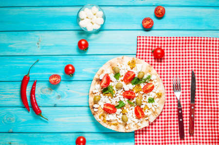 Pita with cheese, cherry tomatoes, olives and greenery on blue wooden background Stock Photo