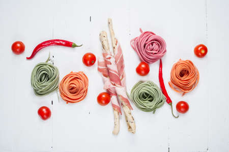 Colorful rolled pasta, cherry tomatoes and bacon on the white wooden background. Top view Stock Photo