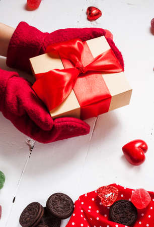Female hands holding gift in red mittens. Stock Photo
