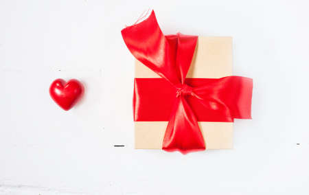 ceramic heart: Gift or present box with red bow ribbon and ceramic heart on wooden table for Valentines day.
