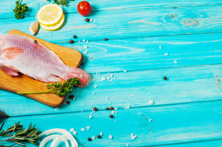fresh tilapia on blue wooden textured background with fresh rosemary and lemon. Culinary mediterranean seafood.