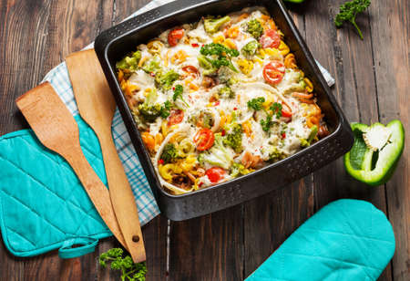 Baked pasta with broccoli and cheesy tomato sauce on wood background