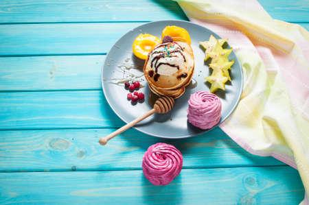 Pancakes with Vanilla Ice Cream on blue wood plate. Stock Photo