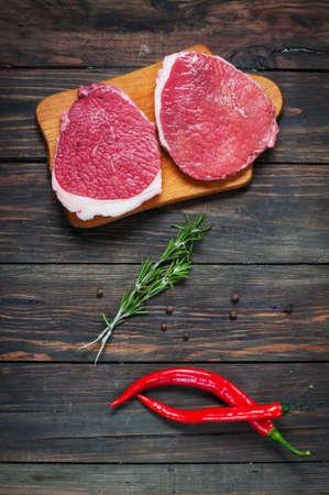 Fresh raw beef steak and chilli pepper on wood