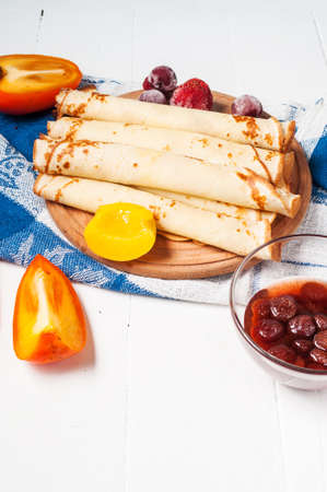 maslenitsa: Pancakes on cutting board on white wooden background. Selective focus.