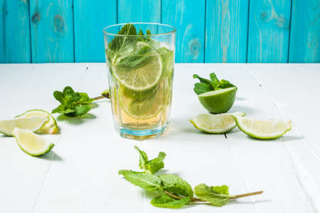 Mojito cocktail with lime and mint in highball glass on a wood table. Blue background. Stock Photo