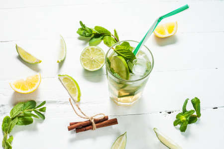 florida citrus: Mojito cocktail with lime and mint in highball glass on a wood white background.