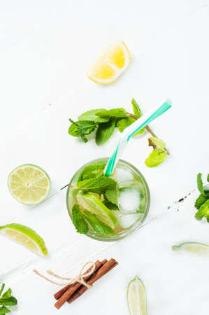 florida citrus: Mojito cocktail with lime and mint in highball glass on a wood white background. Top view