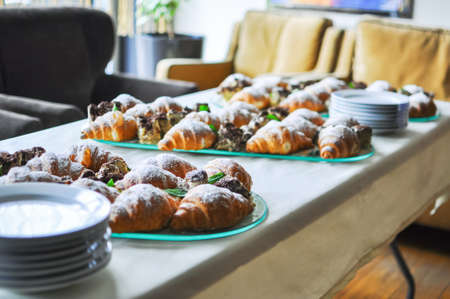 patisserie: Assortment of fresh pastry on table in buffet. Croissants and cakes.