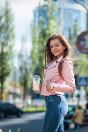 pretty girl with milk shake on the street. Sunset Stock Photo